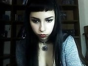 Lusty Goth chick unbuttons her shirt to show you her perky